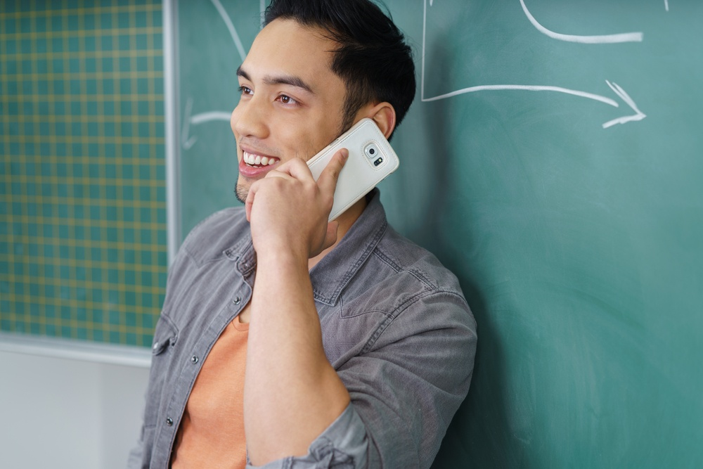 Young Asian man chatting on his mobile as he leans against a chalkboard in a college or university, close up upper body side view